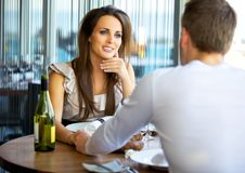 Gorgeous Woman Holding Hands with Her Boyfriend. Portrait of a gorgeous women holding hands with her boyfriend at a fancy restaurant Royalty Free Stock Photos
