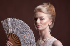 Gorgeous woman holding an oriental fan in hands Stock Photography