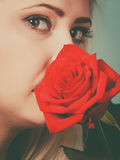 Gorgeous woman holding red rose flower. Royalty Free Stock Image