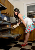 Gorgeous Woman in Kitchen. A fun, 1950s-inspired image of a gorgeous young woman in a dress, apron, and heels, holding a tray that she is either putting in or Royalty Free Stock Photo