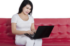 Gorgeous woman with laptop on couch Stock Image