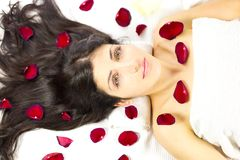 Gorgeous woman laying surrounded by rose petals Royalty Free Stock Photos