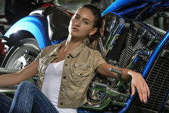 Gorgeous woman leaning against her blue motorcycle. Young beautiful stylish woman taking a break, relaxing near her motorbike Stock Image