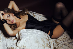 Gorgeous woman with long curly hair wears luxurious lingerie and pantyhose Stock Image