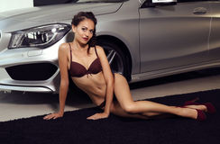 Gorgeous woman with long dark hair wears luxurious lingerie,posing beside a car Stock Photos