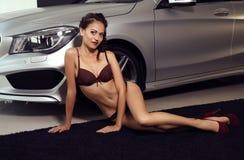 Gorgeous woman with long dark hair wears luxurious lingerie,posing beside a car Stock Photos
