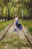 Gorgeous woman in long dress, sunglasses stands between tram rails Stock Image