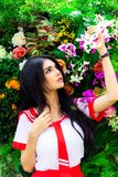 Gorgeous woman looks at beautiful flowers and holds it at a park royalty free stock photography