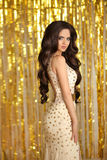 Gorgeous woman in luxury gold. Elegant brunette lady with long w Royalty Free Stock Photo