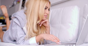 Gorgeous Woman Lying on Couch Busy with her Laptop stock footage