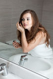 Gorgeous woman makeup in bathroom. Dressed in towel gorgeous woman makeup at modern bathroom royalty free stock photo
