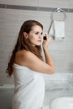 Gorgeous woman makeup in bathroom. Dressed in towel gorgeous woman makeup at modern bathroom royalty free stock images