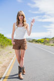 Gorgeous woman making gesture while hitchhiking. On a deserted road in summertime Stock Image