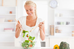 Gorgeous woman mixing a salad Royalty Free Stock Photography