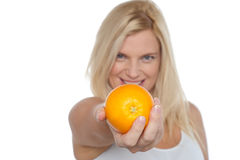Gorgeous woman with an orange in her outstretch arm Royalty Free Stock Image