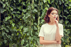 Gorgeous woman in park on green natural background Royalty Free Stock Images