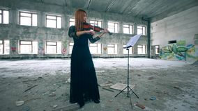 Gorgeous woman is paying the violin from scores. 4K stock video