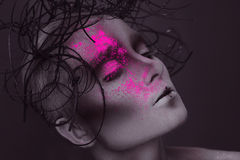 Gorgeous woman with pink neon powder on face Royalty Free Stock Images