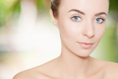 Gorgeous woman portrait cleaning skin over green background Stock Photography