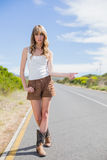 Gorgeous woman posing while hitchhiking. On a deserted road in summertime Royalty Free Stock Images