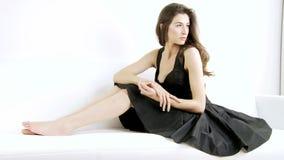 Gorgeous woman posing in studio on sofa