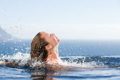 Gorgeous woman raising her head out of the water Stock Images