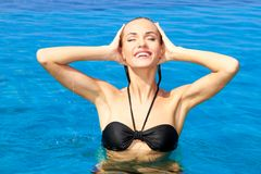 Gorgeous woman raising her head out of the water. In a swimming pool Stock Images