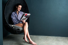 Gorgeous woman reading magazine, sitting on bubble chair Royalty Free Stock Images