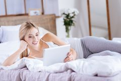 Gorgeous woman reading news from tablet in bed. New discoveries. Charming fair-haired young woman lying on the bed and reading news from her tablet while resting royalty free stock photos