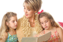 Gorgeous woman reading to her. Shot of a Gorgeous woman reading to her Grandchildren Royalty Free Stock Photos