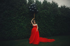 Gorgeous woman in red dress with black balloons Stock Photo