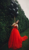 Gorgeous woman in red dress with black balloons Stock Photography