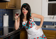 Gorgeous Woman With Red Wine. A retro-looking image of a pretty young woman holding a glass of red wine and smiling at the viewer Stock Photography