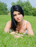 Gorgeous woman relaxing in the grass stock photography