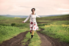 Gorgeous woman running on a countryside road. Freedom concept stock photo