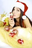 Gorgeous woman santa Claus kissing little christmas toy Stock Photos
