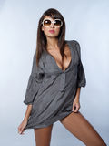 Gorgeous Woman in Sexy Gray Clothes and Shades. Close up Gorgeous Young Woman in Sexy Gray Fashion and Shades  Showing her Cleavage and Sexy Legs. Captured in Royalty Free Stock Photography