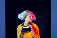 Gorgeous woman shaking her head while holding a device. Close up photo. girl showing her new airstyle, haircut royalty free stock photo