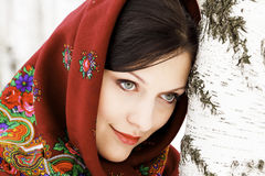 Gorgeous woman in shawl. Gorgeous woman in shawl on her head standing by the birch tree Stock Photography