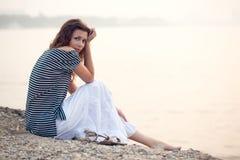 Gorgeous woman sitting on beach. Gorgeous  brunette   woman portrait sitting on stone beach Royalty Free Stock Photo