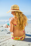 Gorgeous woman sitting on the beach in sunhat applying suncream Royalty Free Stock Photography
