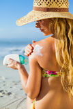 Gorgeous woman sitting on the beach in sunhat applying suncream Royalty Free Stock Photos