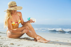 Gorgeous woman sitting on the beach in sunhat applying suncream Stock Photography