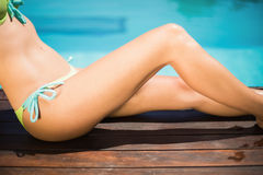Gorgeous woman sitting by poolside. On a sunny day Royalty Free Stock Photo