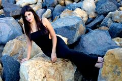 Gorgeous woman sitting on rocks with black dress amd long hair Stock Photos
