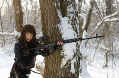 Gorgeous woman with a sniper rifle. Gorgeous young woman with a sniper rifle near the tree Stock Photo
