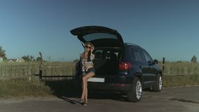 Elegant woman posing near car in countryside. Gorgeous woman in stylish outfit posing while sitting in car trunk in countryside at sunset during summer vacation stock video