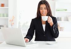 Gorgeous woman in suit enjoying a cup of coffee. While relaxing with her laptop in the kitchen Royalty Free Stock Image