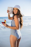 Gorgeous woman in swimsuit holding cocktail looking over shoulde Stock Photography