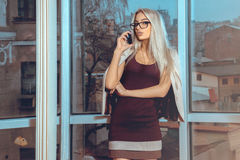 Gorgeous woman talking on the phone by the window overlooking th Stock Photo